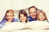 自宅の毛布の下の 2 人の子供と幸せな家庭 — ストック写真