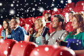Happy friends with popcorn and drinks in cinema — Stockfoto
