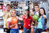 Happy friends in bowling club showing thumbs up — Stock Photo
