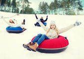 Group of happy friends sliding down on snow tubes — Stock Photo