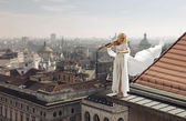 Woman playing the violin on the top of the edge of the roof — Stock Photo