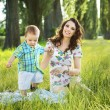 Pretty mother playing with her son on the blanket — Stock Photo #55229283