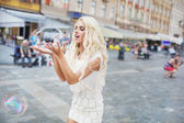 Cheerful blonde carrying huge soap bubble — 图库照片