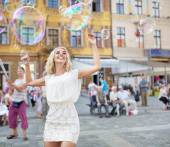 Cheerful young woman catching the soap bubbles — Stock Photo
