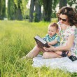 Mother with curly hairstyle reading fairy tales for baby — Stock Photo