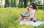 Mother with curly hairstyle reading fairy tales for baby — Foto de Stock