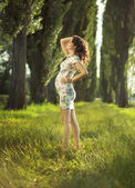 Portrait of the pregnant woman in the park — Stock Photo