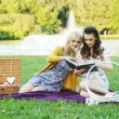Two women reading book in the park — Stock Photo #55245635