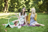 Two cheerful girlfriends enjoying the spare time in park — Stockfoto