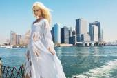 Woman wearing ragged dress with the city in the background — Stock Photo