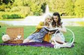 Two women reading book in the park — Stock Photo