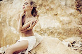 Sensual pale lady posing over the rocks — Stock Photo