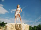 Woman in white posing on the rocks — Stock Photo