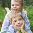 Two litle brothers relaxing on a grass — Stock Photo #56674371
