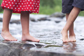 Children soaking feet in a brook — Foto Stock