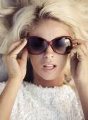 Fine portrait of the woman putting on the sunglasses — Stock Photo