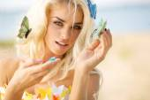 Pretty blond lady with colorful butterflies — Stock Photo