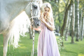Blond cute woman with a horse — Stock Photo