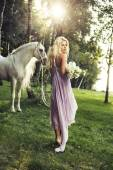 Blond nymph with flowers and horse — Stock Photo