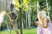 Beautiful woman taking pictures of the horse — Stock Photo