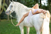 Relaxed woman lying on the horse — Stock Photo