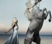 Blond nymph posing with majestic horse — Stock Photo