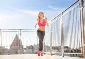 Charming, athletic woman running on the roof — Stock Photo