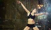 Sensual woman dancing in a fountain — Stock Photo