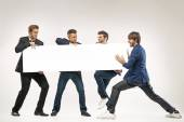 Four guys pushing the billboard — Stock Photo