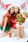 Two smiling sisters wearing santa hats — Stock Photo