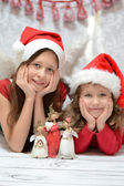 Two glad sisters with santa caps — Stock Photo