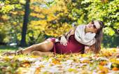 Smart pregnant woman in the autumn park — Stock Photo