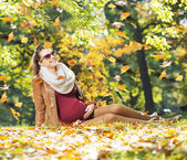 Smiling lady watching flying leaves — Stock Photo
