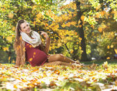 Art picture of pregnant lady under the leaves rain — Stock Photo