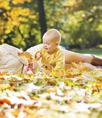 Little child playing autumn leaves — Stock Photo