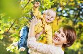 Charming wife carrying little child — Stock Photo