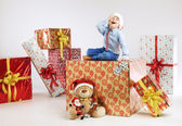 Surprised small santa on the presents — Stock Photo