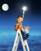 Little boy collecting shining stars — Stock Photo