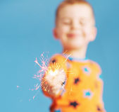 Blurred portrait of boy holding a sparkler — Stock Photo