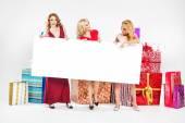 Three attractive women holding empty board — Stock Photo