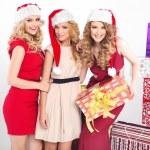 Three alluring women wearing Christmas hats — Stock Photo #60360229