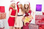 Three alluring women wearing Christmas hats — Stock Photo