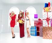 Three attractive girls with lots of gifts — Stock Photo