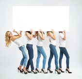 Shapely women carrying empty board — Stock Photo