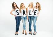 Four attractive women promoting sale — Stock Photo