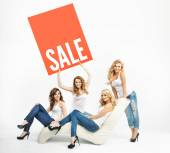 Attractive women promoting middle-season sale — Stock Photo