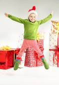 Cute jumping elf with presents in the bacground — Stock Photo