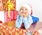 Charming little boy lying on present — Stock Photo