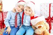 Two smiling little brothers among presents — Stock Photo