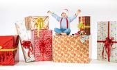 Small cute boy on plenty of presents — Stock Photo